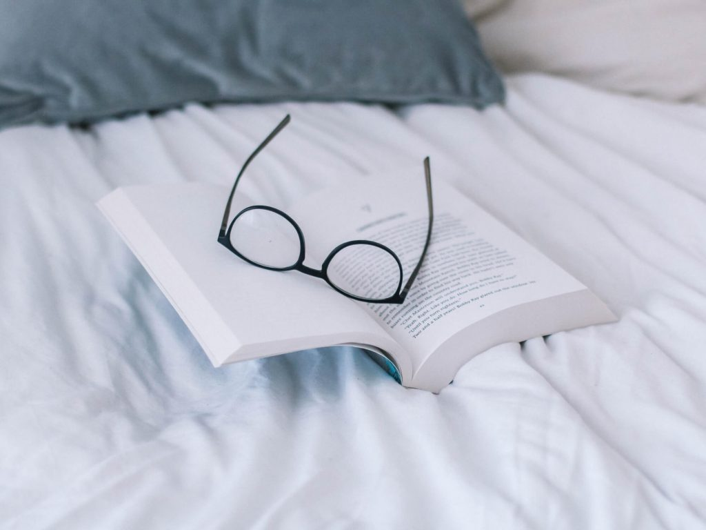 En bok och glasögon i en säng