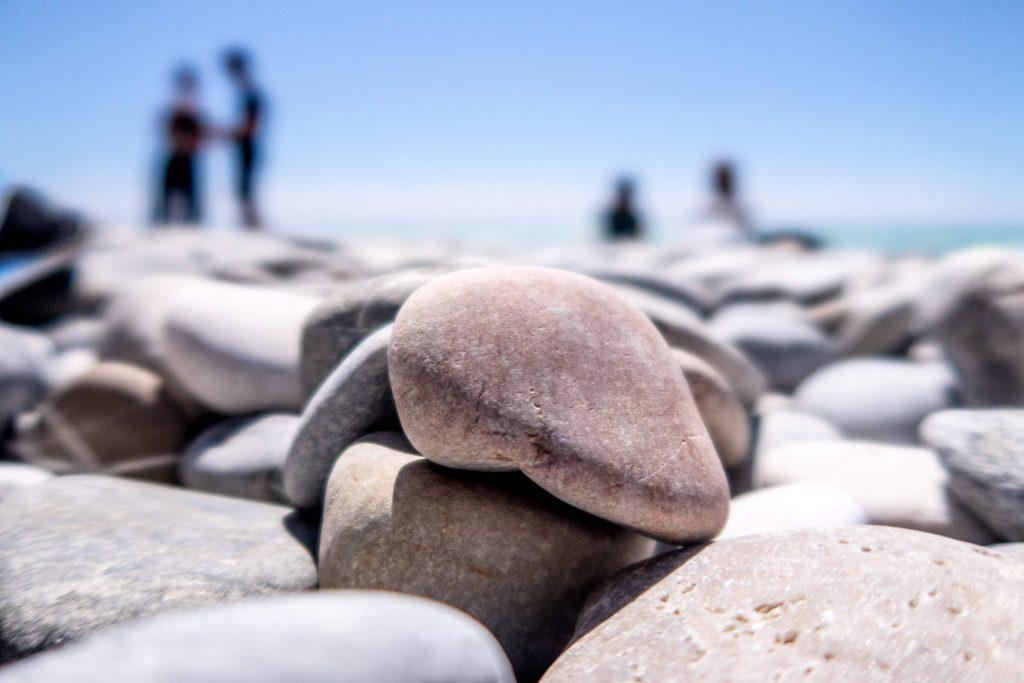 En strand med stenar med personer i bakgrunden